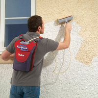 Man using a backpack paint roller system