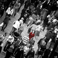 A lady in a red dress in a grey crowd of people